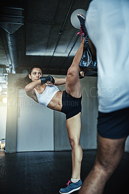 Buy stock photo Shot of a young woman sparring with a boxing partner at the gym