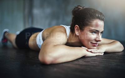 Buy stock photo Shot of a sporty young woman resting during her workout routine at the gym