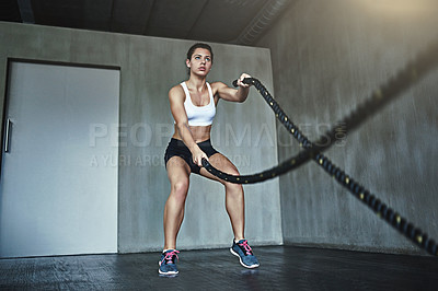 Buy stock photo Shot of a sporty young woman working out with heavy ropes at the gym