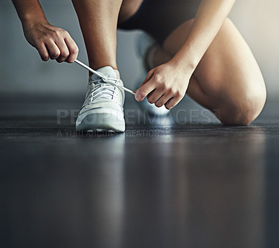 Buy stock photo Cropped shot of a woman tying her shoelaces before a workout