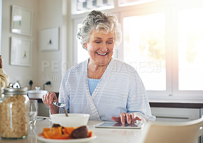 Buy stock photo Cropped shot of a senior woman using a digital tablet while having breakfast at home