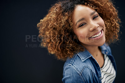 Buy stock photo Portrait of a young woman posing against a dark background