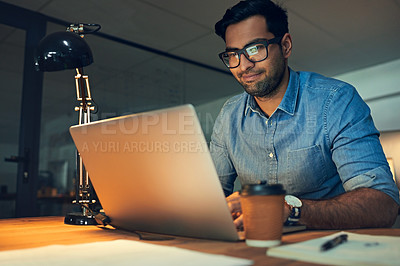 Buy stock photo Cropped shot of a young businessman working late on a laptop in an office