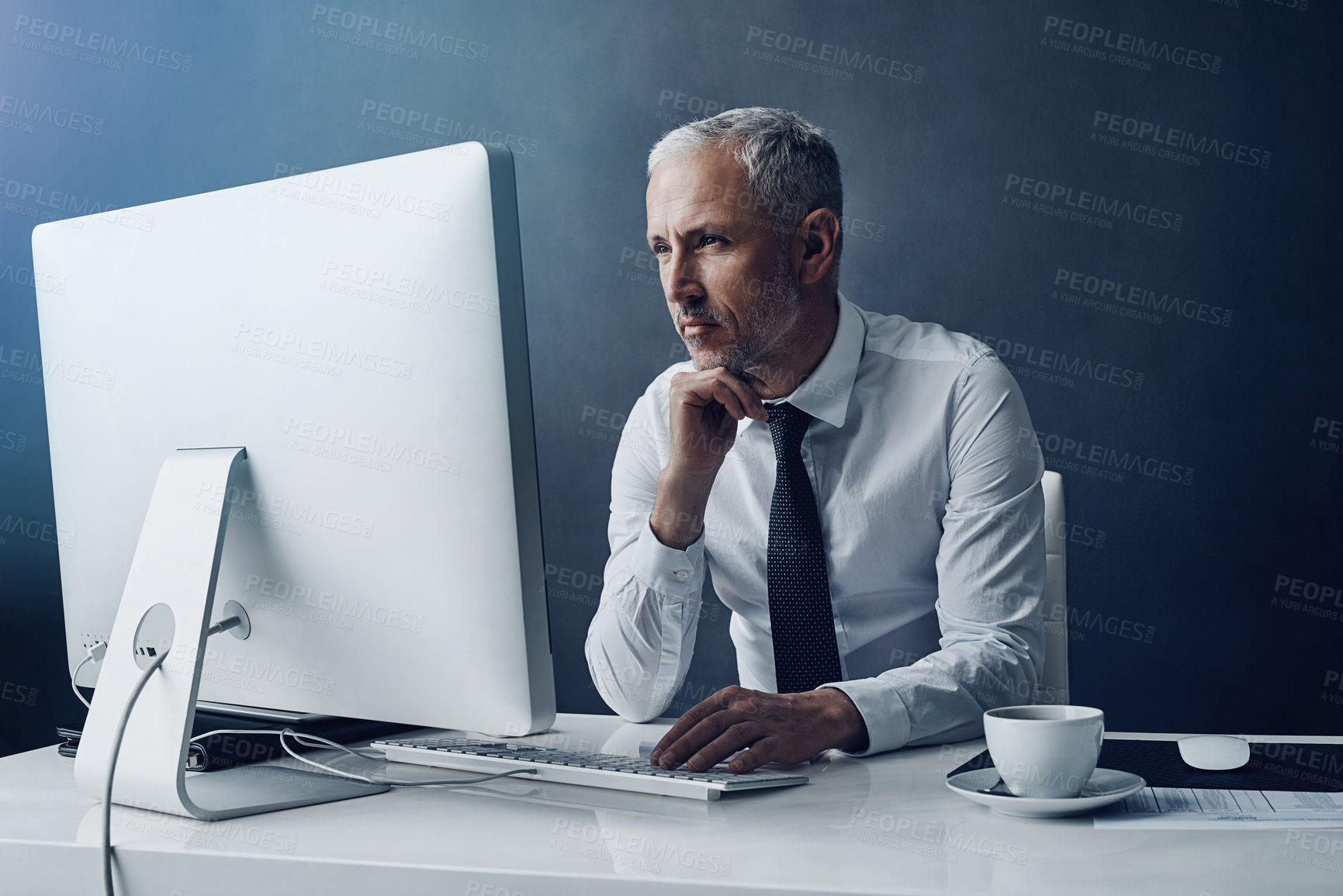 Buy stock photo Cropped shot of a mature businessman working on his computer