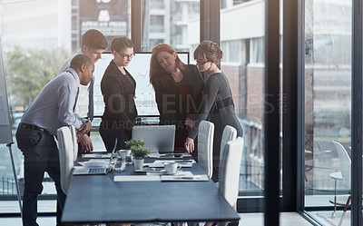 Buy stock photo Shot of a group of businesspeople talking together over a laptop while having a meeting in a boardroom