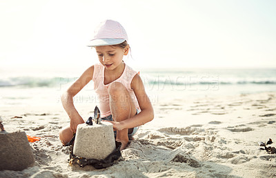 Buy stock photo Shot of a little girl building a sand castle on her own at the beach