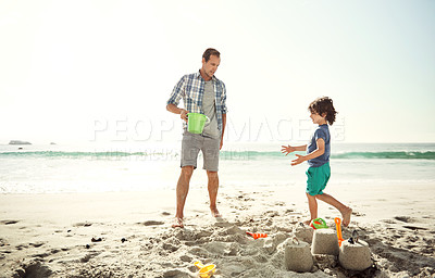 Buy stock photo Shot of a father building a sandcastle on the beach with his young son