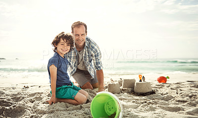 Buy stock photo Portrait of a father building a sandcastle on the beach with his young son