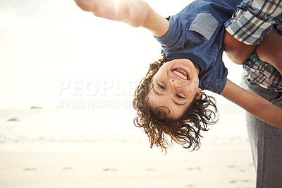 Buy stock photo Portrait of a happy little boy being held upside down by his father