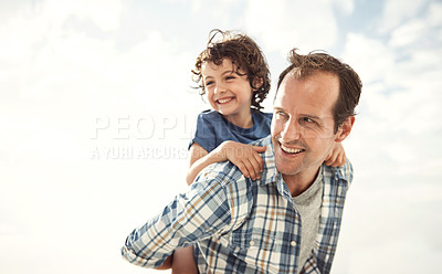 Buy stock photo Shot of a father and son enjoying a piggyback ride on the beach