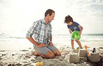 Buy stock photo Shot of a happy little boy building a sandcastle on the beach