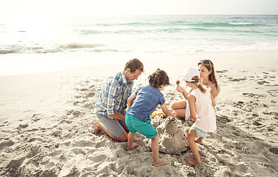 Buy stock photo Shot of a family with young children building a sandcastle together on the beach