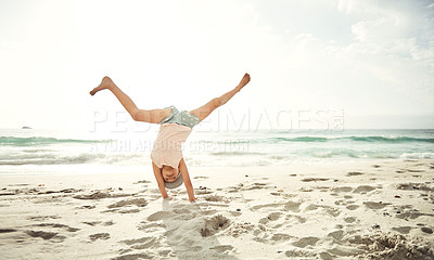 Buy stock photo Shot of an excited little girl doing a cartwheel on the beach
