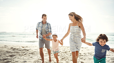 Buy stock photo Shot of a young family holding hands while running on the beach