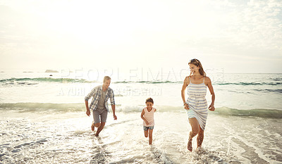 Buy stock photo Shot of a happy young family running on the beach