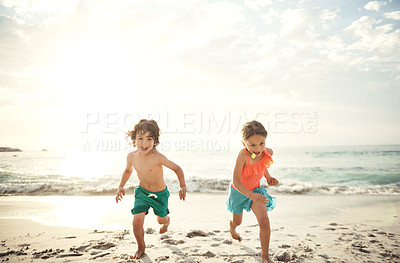 Buy stock photo Shot of a little brother and sister running along the beach in the late afternoon