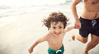 Buy stock photo Shot of a father running hand in hand with his little son on the beach in the late afternoon