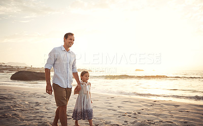 Buy stock photo Shot of a father holding his little girl's hand as they walk on the beach at sunset