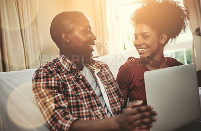 Buy stock photo Cropped shot of a young couple browsing together on a laptop at home
