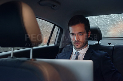 Buy stock photo Shot of a businessman sitting in the backseat of a car working on a laptop