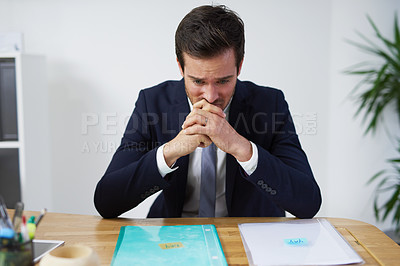 Buy stock photo Shot of a nervous looking businessman sitting at a desk trying to decide on which report to use