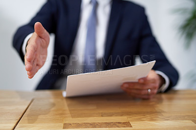 Buy stock photo Cropped shot of a businessman sitting at a desk and holding paperwork extending a handshake