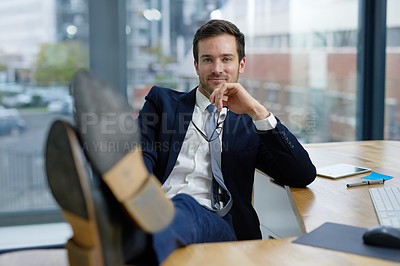 Buy stock photo Portrait of a businessman sitting in an office with his feet resting on his desk