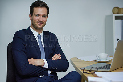 Buy stock photo Portrait of a confident young businessman sitting with his arms crossed at a desk in an office