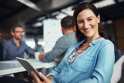 Buy stock photo Portrait of a woman sitting at a table in an office using a digital tablet with colleagues working in the background