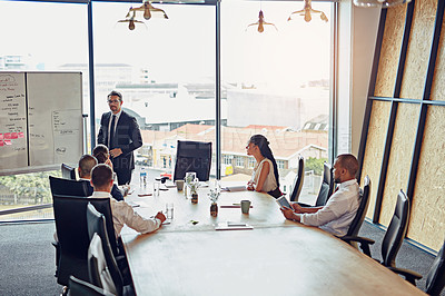 Buy stock photo Shot of an executive giving a whiteboard presentation to a group of colleagues in a boardroom