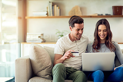 Buy stock photo Shot of a happy young couple making a credit card payment on a laptop together at home