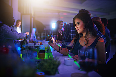Buy stock photo Cropped shot of a young woman texting on her cellphone while standing in a nightclub