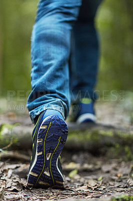 Buy stock photo Shot of an unidentifiable young man hiking through the forest