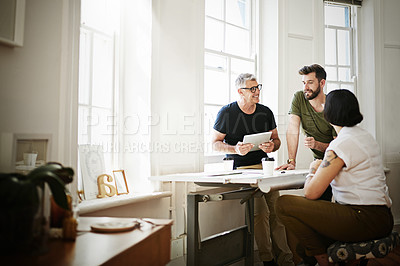 Buy stock photo Shot of a group of designers using a tablet while brainstorming in the office