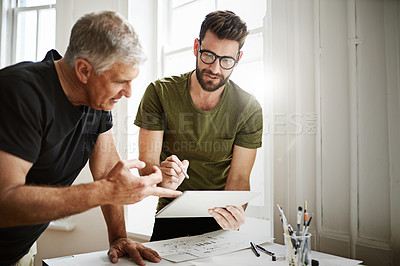 Buy stock photo Shot of two designers using a tablet while brainstorming in the office