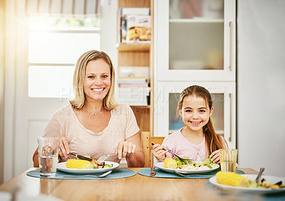 Buy stock photo Portrait of a happy mother and daughter enjoying a meal together at home