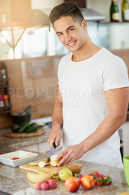 Buy stock photo Cropped shot of a young man making a fruit salad in his kitchen