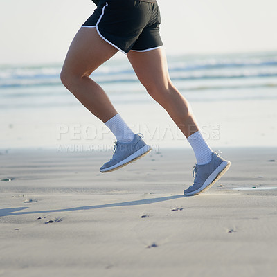 Buy stock photo Cropped shot of an unrecognizable young man running on the beach