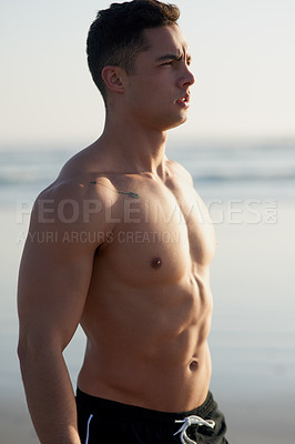 Buy stock photo Cropped shot of a handsome young man standing shirtless at the beach