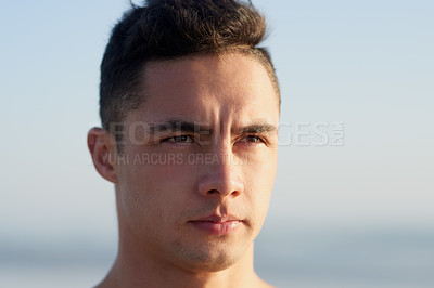 Buy stock photo Cropped shot of a handsome young man at the beach