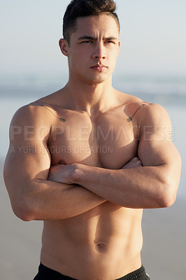 Buy stock photo Cropped shot of a handsome young man standing with his arms folded at the beach