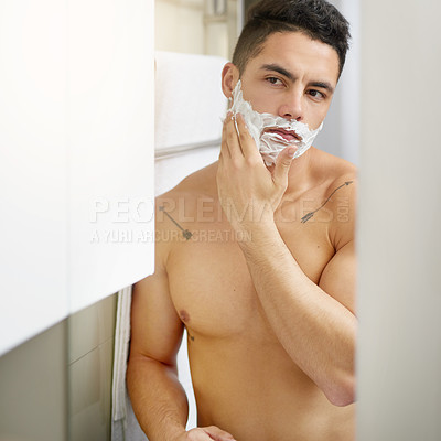 Buy stock photo Shot of a young man applying shaving cream to his face