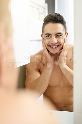 Buy stock photo Shot of a young man touching his face after shaving