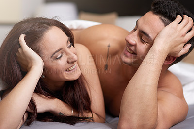 Buy stock photo Shot of a young couple relaxing in bed together