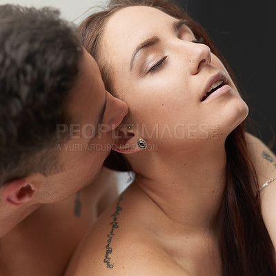 Buy stock photo Shot of a young man lovingly kissing his girlfriend's ear