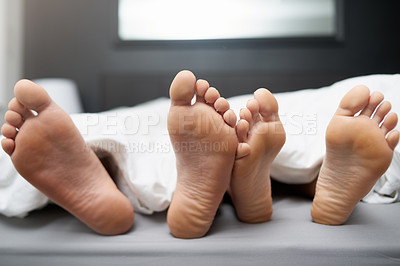 Buy stock photo Shot of a couple's feet poking out from under the bed sheets