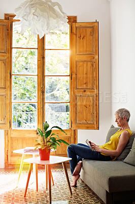 Buy stock photo Shot of a mature woman sitting in her living room using a digital tablet