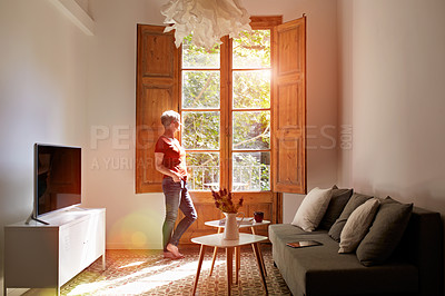 Buy stock photo Shot of a mature woman standing by a window at home