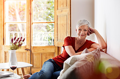 Buy stock photo Portrait of a smiling mature woman relaxing on her sofa at home with a glass of wine