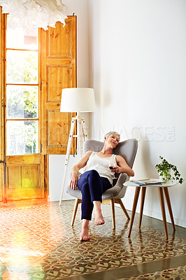 Buy stock photo Shot of a smiling mature woman relaxing on a chair at home with a glass of wine